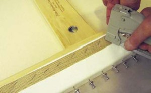 12. Stapling through a woven band cushions the canvas and facilitates future staple removal.