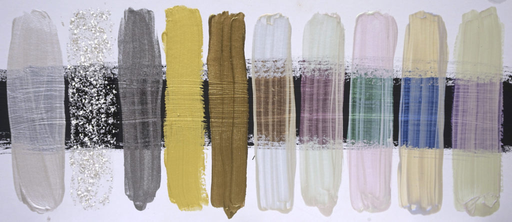 A selection of Iridescent and Interference colors on a white board with a center area of Black Gesso. Colors from left to right: Iridescent Pearl(Fine), Pearl Mica Flake(Small), Stainless Steel(Fine), Iridescent Gold (Fine), Iridescent Bronze(Fine), Interference Orange, Interference Red, Interference Green, Interference Blue, Interference Violet.